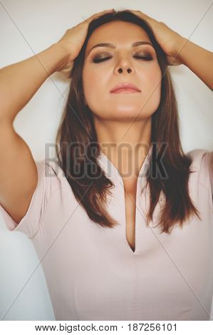 Close up portrait of young beautiful woman with professional makeup, eyes closed, hand holding head