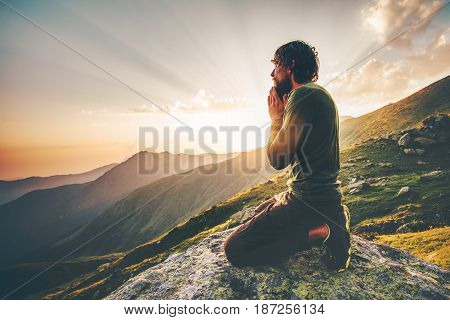 Man praying at sunset mountains Travel Lifestyle spiritual relaxation emotional concept vacations outdoor harmony with nature landscape