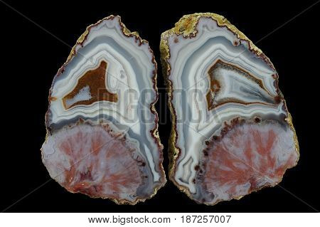 A cross section of the agate stone. At the top is concentric agate at the bottom pseudomorphosis after the spheroidal concentration of minerals. Multicolored silica rings colored with metal oxides are visible. Origin: Asni Atlas Mountains Morocco.