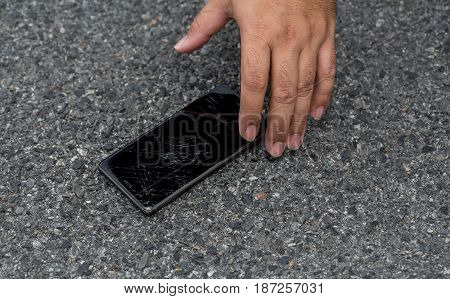 Hand Picking Smart Phone with broken screen on the Ground