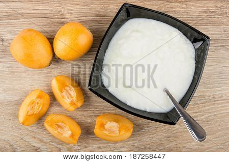 Pieces Of Loquat, Bowl With Yogurt And Spoon On Table
