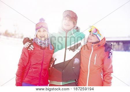 Young man with female friends standing arm around in snow