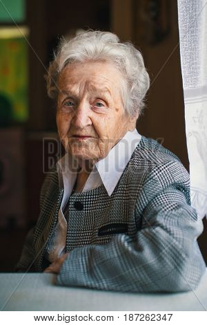 An elderly woman in the his house.