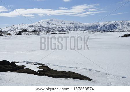 View over a frozen lake with snowmobile tracks and a Sami village and a snowy mountain in background picture from the North of Norway.