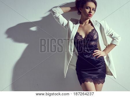 Young sexy beautiful woman wearing black pumps, silk nightie and white coat standing and posing against white wall. Sensual fashion vogue style portrait. Toned colors.
