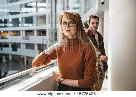 Young and handsome man and woman standing inside modern business center