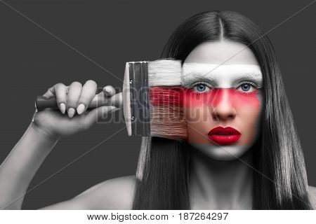 Portrait of a woman painting with a brush on her face