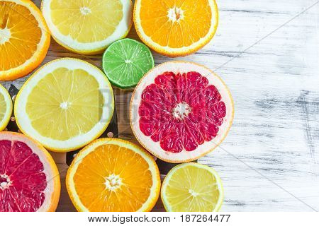 Fresh choped slices of different types of citrus on the white table