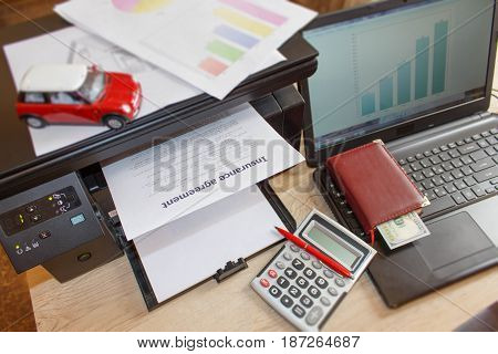 Homeowner and car Insurance form with Laptop Printer pen dollars calculator on the table. Insurance concept