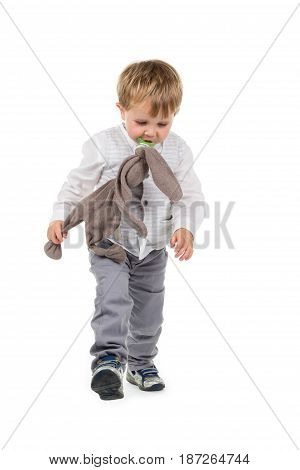 Toddler (boy) with brown plush animal (rabbit) and pacifier walking. Isolated on white background