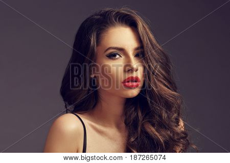 Pretty seductive girl in black silk nightie and white coat sitting and posing on white background. Fashion portrait.