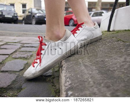 Woman in white tennis shoes stepping off a curb onto a cobbled street with cars in background