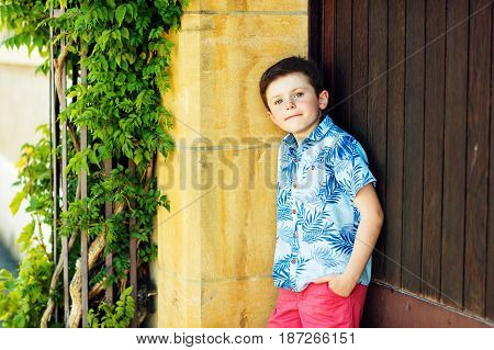 Funny stylish kid boy posing outdoors, wearing blue print shirt and red shorts