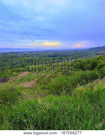 The May landscape made in the equipment of a vertical panorama. The sky tightened dense clouds, and below the green wood and hills of Krasnodar Krai.