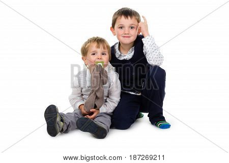 2 Little brothers wearing festive clothing sitting together on the ground. One points 1 finger up in the air the other has a brown plush animal (rabbit) and pacifier. Isolated on white background