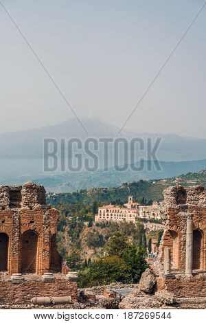 Scenic view of Taormina, Sicily , Italy with the famous ruins of the ancient Greek Theatre in the foreground and Mount Etna volcano in the distance