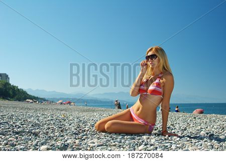 Young beautiful girl in swimsuit posing as model on beach of pebbles by the sea