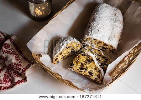 Sliced Christmas stollen on parchment paper in wicker basket lit candle linen towel minimalist style moody top view