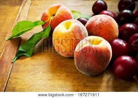 Beautiful ripe sweet peaches and plums on table