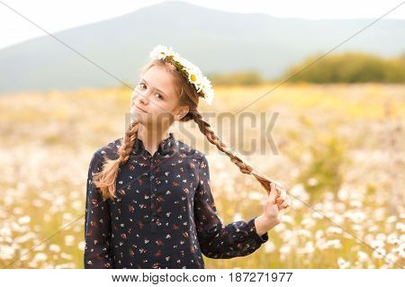 Smiling blonde teenage girl 14-16 year old posing outdoors. Looking at camera. Childhood.