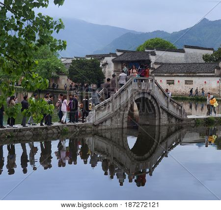 HONGCUN CHINA - APRIL 20 2014: Tourist walking around Moon Lake in Hongcun Village China. Hongcun is ancient village in Anhui Province near the southwest of Mount Huangshan.