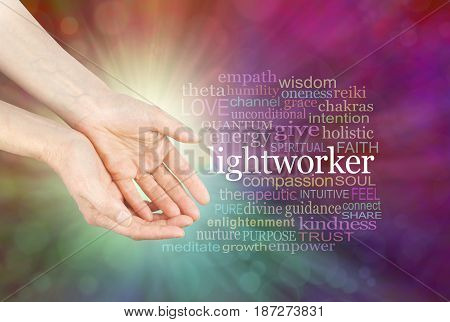 The healing hands of a Lightworker  - Female hands in open gesture beside the word LIGHTWORKER and a relevant word cloud  on a radiating multi-coloured bokeh background