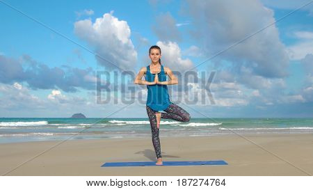 The girl is making yoga pose on beach in Vietnam. Sea or ocean happy woman relaxation. Water and waves. Hands and blue sky. Exercises calmness and harmony.