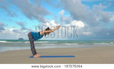 Woman practicing yoga on the beach at sunset. Healthy lifestyle. Exercises calmness and harmony.