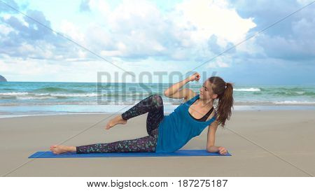 Young woman training on the beach in front of sea. Morning gymnastic. Side plank exercise. Healthy active lifestyle concept.