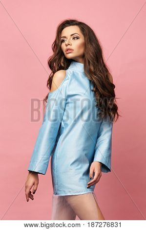 Pretty stylish girl with long curly hair wearing classy beautiful blue dress and posing against pink background. Fashion vogue style full lenght portrait of young beautiful woman
