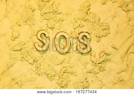 SOS message in block letters in the sand.