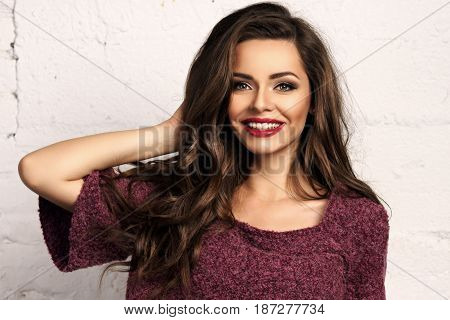Young beautiful gorgeous female model in purple pullover posing against white brick wall. Stunning glamorous happy joyfull smiling girl with long curly hair