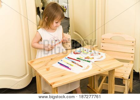 Active little preschool age child, cute toddler girl with blonde curly hair, drawing picture on paper using colorful pencils and felt-tip pens, sitting at wooden table indoors at home or kindergarten.