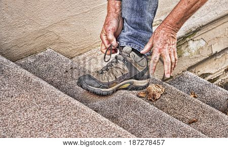 Man stopping on his way up the concrete stairs, tying his shoe lace, showing a leg wearing sport shoes and his hands tying the lace.