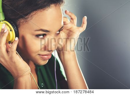 beautiful young black woman with headphones wearing green