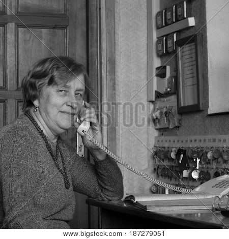 An elderly woman talking on a landline phone and her workplace desk and many Keys on the wall fire alarm and instructions on the wall