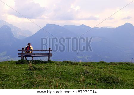 Travel To Sankt-wolfgang, Austria. The Young Man Are Sitting On A Bench With View On The Mountains.