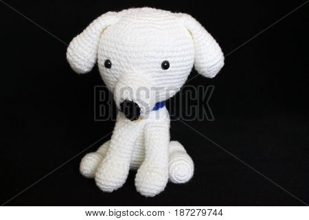 White dog toy hand-crocheted posed on black background