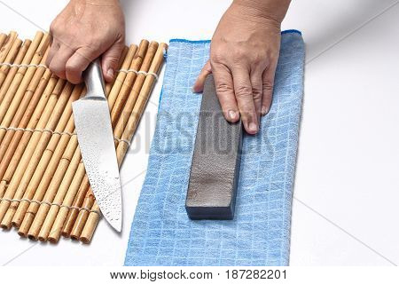 HomemadeMaid to sharpen a knife with spray water and whetstone.