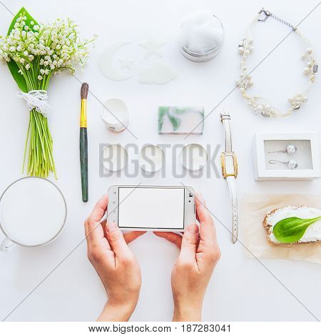 Beauty Blog Concept. Close Up Female Hands Keep The Smartphone On The Background Of Styled Greenery