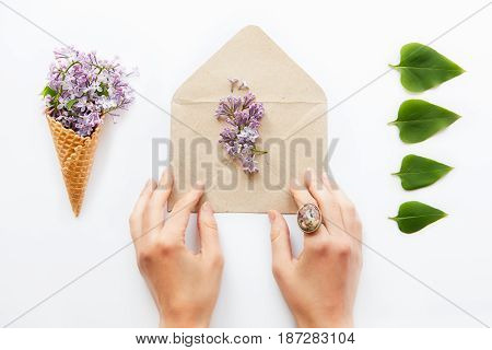 Close Up Women Hands Touching Opened Craft Paper Envelope Filled With Purple Lilac Flowers Surrounde