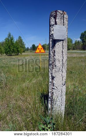 Soviet vintage geodesic sign.Radioactivity sign behind.May 19, 2017.Chernobyl area.Kiev region.Ukraine