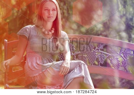 Beautiful young woman sitting on bench in park