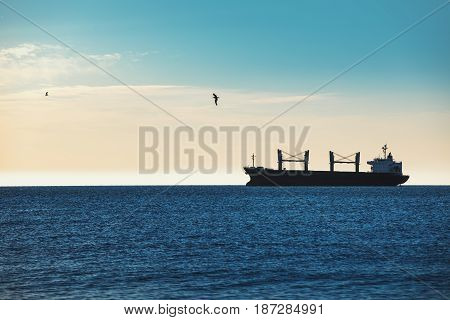 Cargo ship sailing in ocean and blue sky on the background