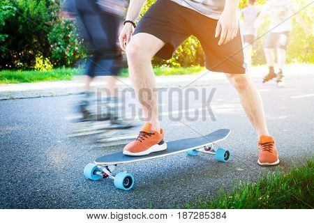 Young man riding on a longboard. Longboard on the road in sunny weather. People around skateboard. Pathway in a park. Urban scene.