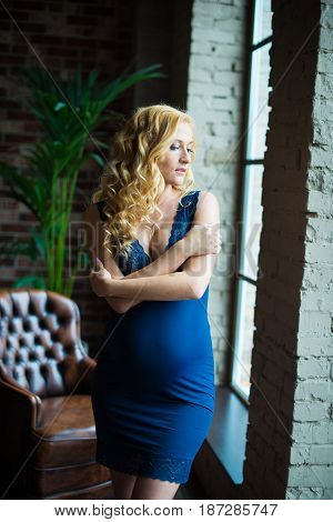 A beautiful pregnant girl stands near a window and looks at her tummy