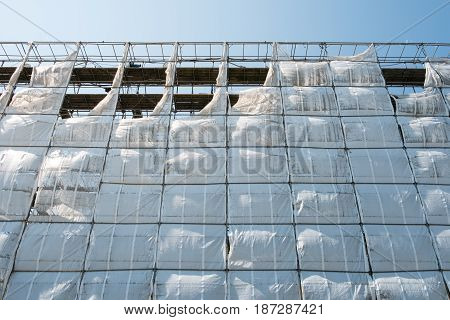 Scaffolding With White Canvas And Blue Sky Background