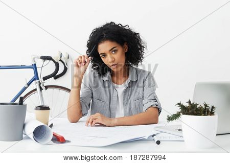 Photo Of Dark-skinned Office Worker Having Dark Short Curly Hair And Brown Eyes Making Report Having