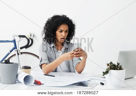 Dissatisfied Business Woman With Dark Skin And Voluminous Hair Sitting At Her Office Using All Moder