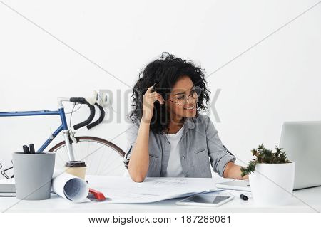 Positive Young Beautiful American Woman Wearing Stylish Shirt And Big Round Glasses Making Drawings